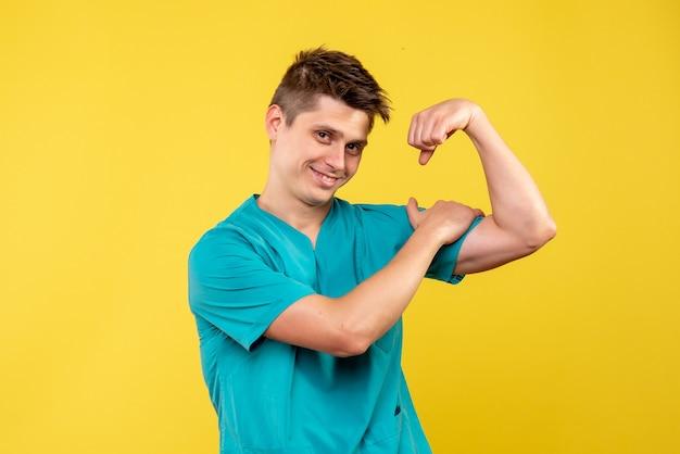 Vooraanzicht van mannelijke arts in medisch kostuum die op gele muur buigen