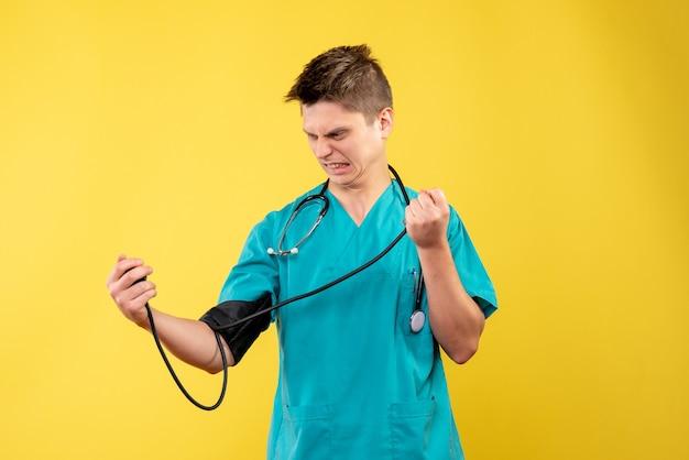 Vooraanzicht van mannelijke arts in medisch kostuum die zijn druk op gele muur controleren