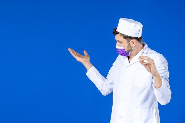 Vooraanzicht van mannelijke arts in medisch kostuum en de injectie van de maskerholding op blauw