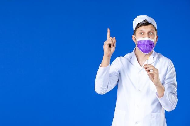 Vooraanzicht van mannelijke arts in medisch kostuum en de purpere injectie van de maskerholding op blauw