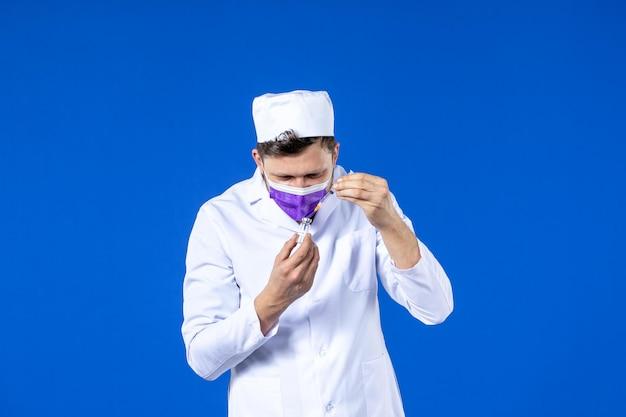Vooraanzicht van mannelijke arts in medisch kostuum en masker die de injectie met vaccin op blauw proberen te vullen