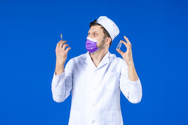 Vooraanzicht van mannelijke arts in medisch kostuum en masker met injectie en vaccin op blauw