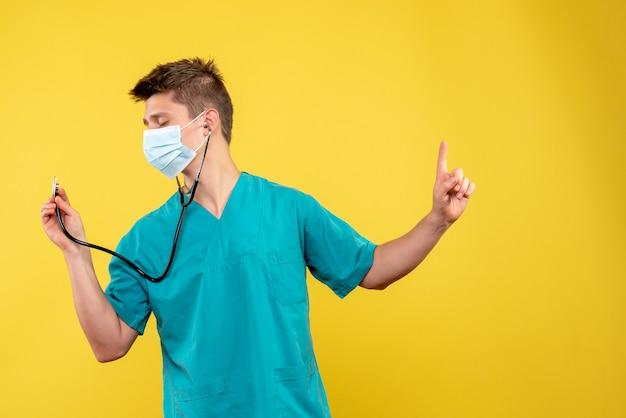 Vooraanzicht van mannelijke arts in medisch kostuum en masker met stethoscoop op gele muur