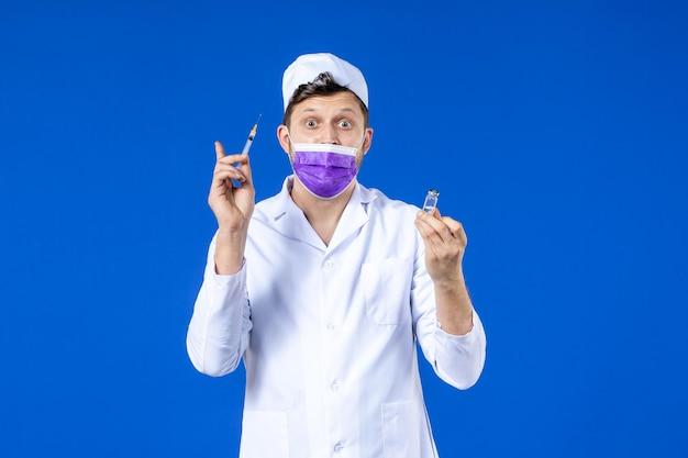 Vooraanzicht van mannelijke arts in medisch kostuum en masker met vaccin en injectie op blauw