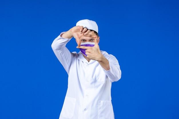 Vooraanzicht van mannelijke arts in medisch kostuum en paars masker op blauw