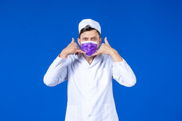 Vooraanzicht van mannelijke arts in medisch kostuum en purper masker die telefoongesprek poseonblauw tonen