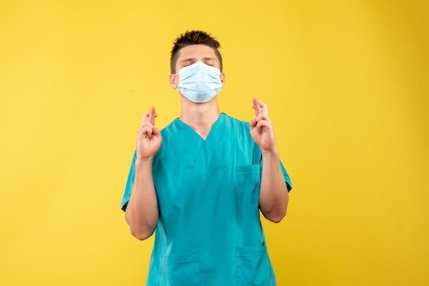 Vooraanzicht van mannelijke arts in medisch kostuum en steriel masker die op gele muur hopen