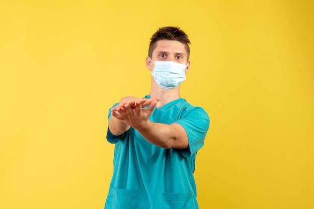 Vooraanzicht van mannelijke arts in medisch kostuum en steriel masker op gele muur