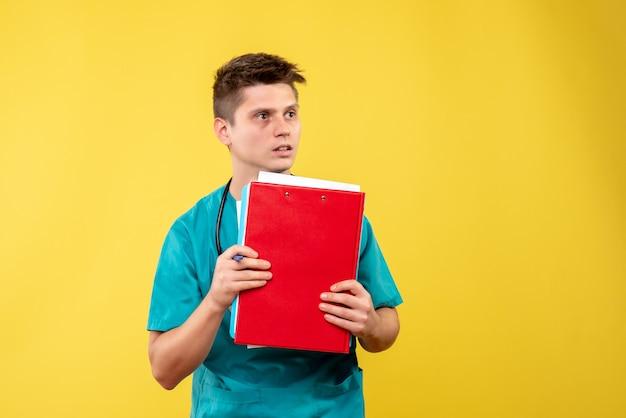 Vooraanzicht van mannelijke arts in medisch kostuum met analyse op gele muur