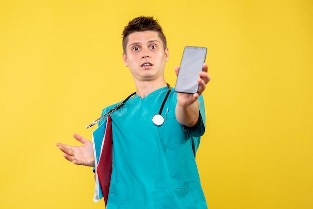 Vooraanzicht van mannelijke arts in medisch kostuum met telefoon en nota over gele muur