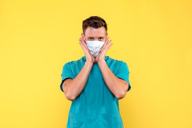 Vooraanzicht van mannelijke arts in steriel masker op gele muur
