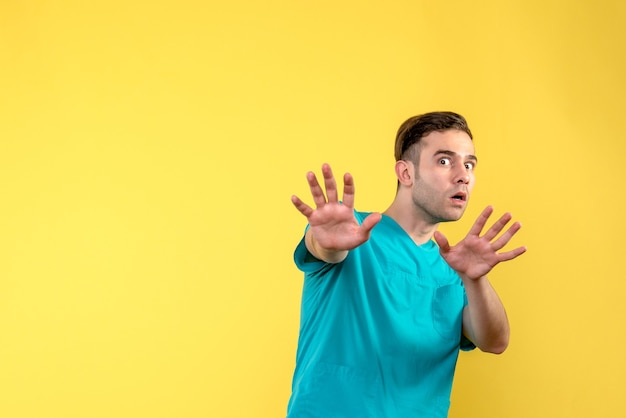 Vooraanzicht van mannelijke arts met bang uitdrukking op gele muur