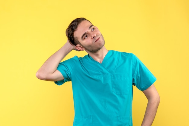 Vooraanzicht van mannelijke arts met beklemtoond gezicht op gele muur