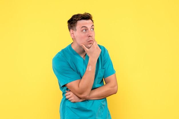 Vooraanzicht van mannelijke arts met denkende uitdrukking op gele muur