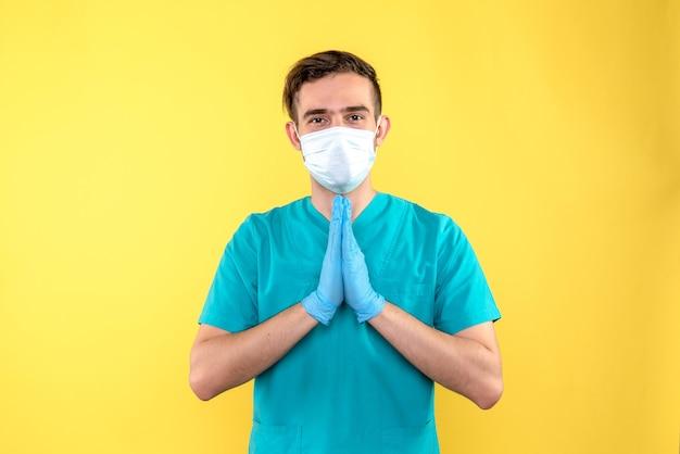 Vooraanzicht van mannelijke arts met handschoenen en masker op gele muur