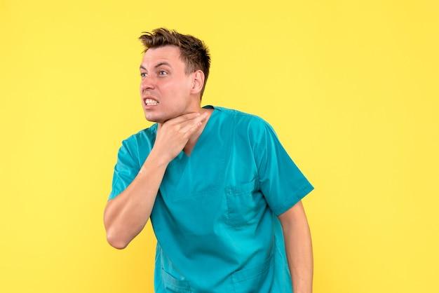 Vooraanzicht van mannelijke arts met keelpijn op gele muur