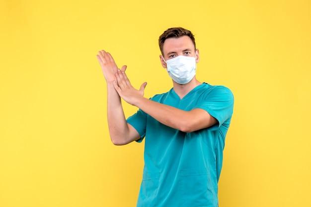 Vooraanzicht van mannelijke arts met masker dat op gele muur klapt