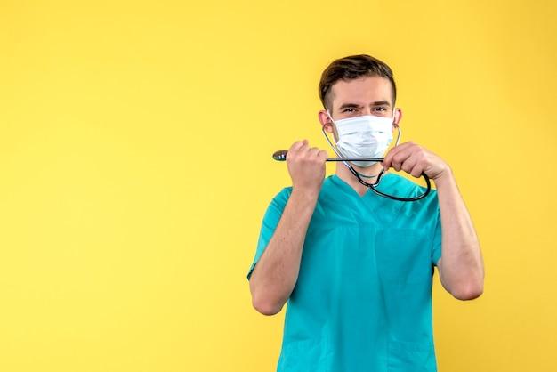 Vooraanzicht van mannelijke arts met stethoscoop en masker op gele muur