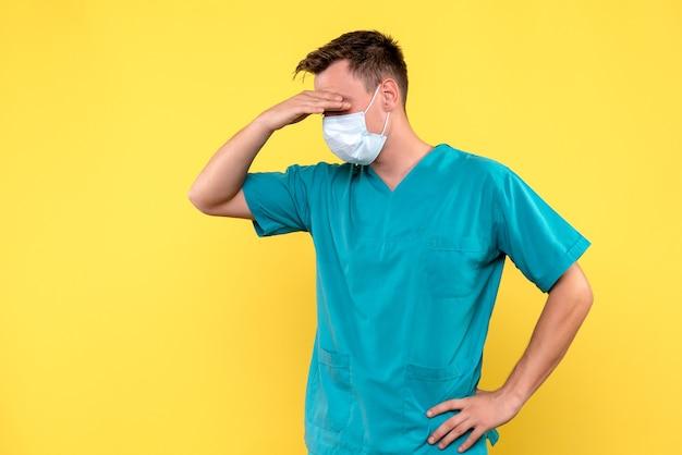 Vooraanzicht van mannelijke arts met stressvolle uitdrukking op gele muur