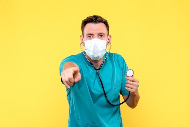 Vooraanzicht van mannelijke arts met tonometer en masker op gele muur
