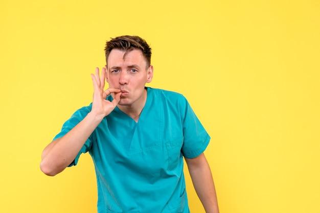 Vooraanzicht van mannelijke arts op gele muur