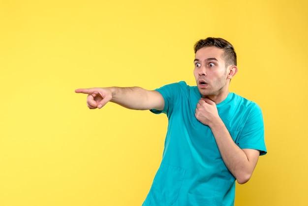 Vooraanzicht van mannelijke arts verrast op gele muur