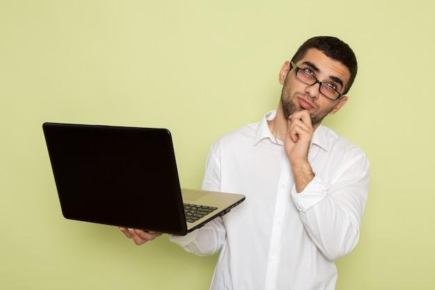 Vooraanzicht van mannelijke beambte die in wit overhemd zijn laptop houden en gebruiken die aan de lichtgroene muur denken