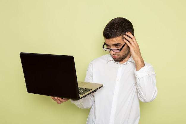 Vooraanzicht van mannelijke beambte in wit overhemd die zijn laptop op de lichtgroene muur met behulp van