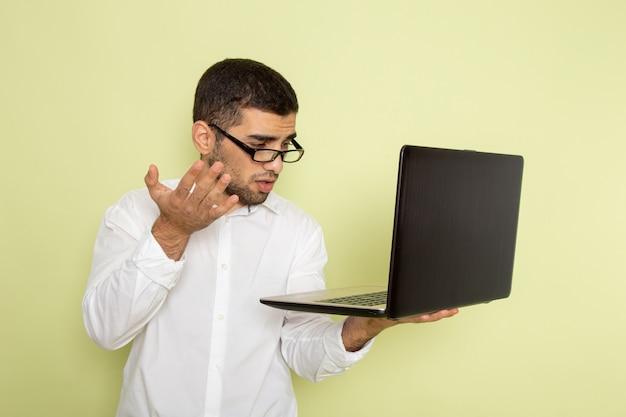 Vooraanzicht van mannelijke beambte in wit overhemd die zijn laptop op groene muur met behulp van