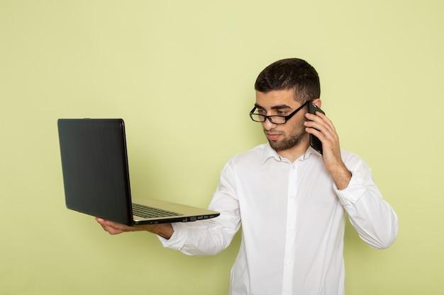 Vooraanzicht van mannelijke beambte in wit overhemd met laptop die aan de telefoon op groene muur spreekt