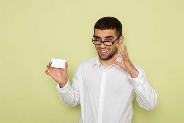 Vooraanzicht van mannelijke beambte in wit overhemd met witte kaart op de lichtgroene muur