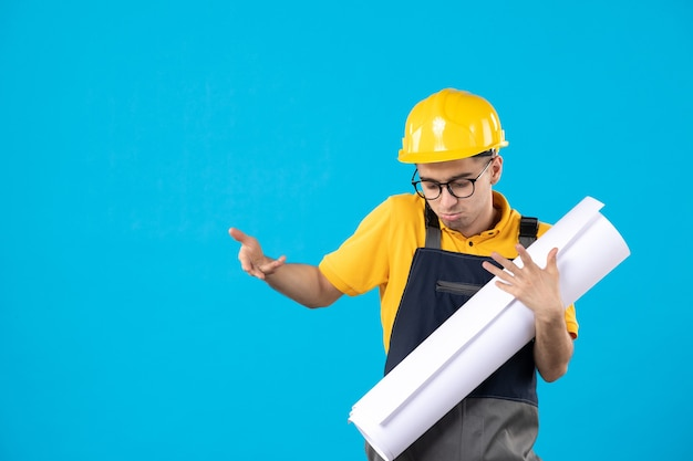 Vooraanzicht van mannelijke bouwer in geel uniform en helm met plan op blauwe muur