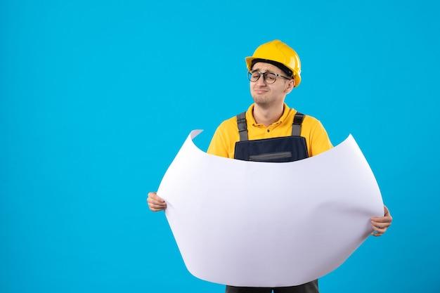 Vooraanzicht van mannelijke bouwer in geel uniform leesplan op blauw