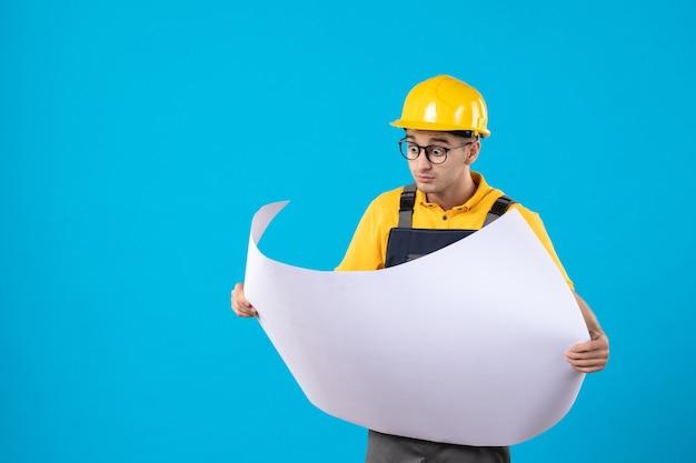 Vooraanzicht van mannelijke bouwer in geel uniform lezingsdocument plan op blauw