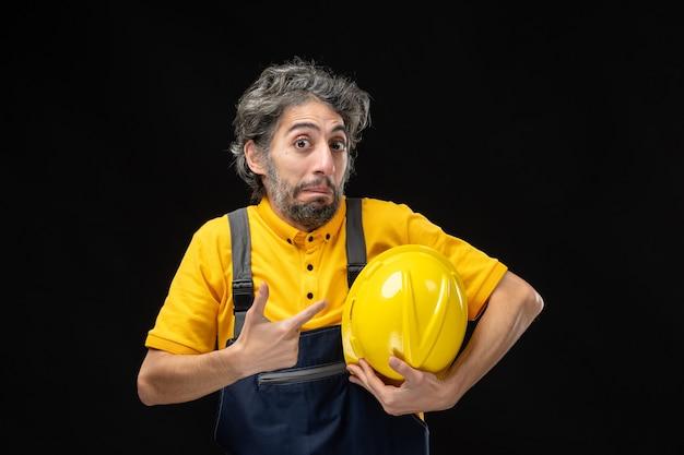 Vooraanzicht van mannelijke bouwer in geel uniform op de zwarte muur