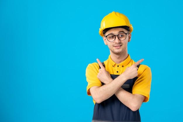 Vooraanzicht van mannelijke bouwer in uniform en helm op blauwe ondergrond