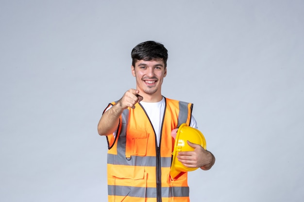Vooraanzicht van mannelijke bouwer in uniform met beschermende helm op witte muur