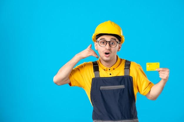 Vooraanzicht van mannelijke bouwer in uniform met gele creditcard in zijn handen op blauwe muur