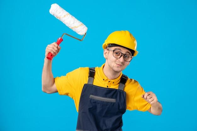 Vooraanzicht van mannelijke bouwer in uniform met verfroller in zijn handen op blauwe ondergrond