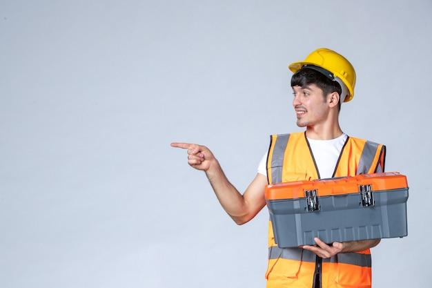 Vooraanzicht van mannelijke bouwer in uniform met zware gereedschapskoffer op witte muur