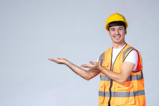 Vooraanzicht van mannelijke bouwer in uniform op witte muur