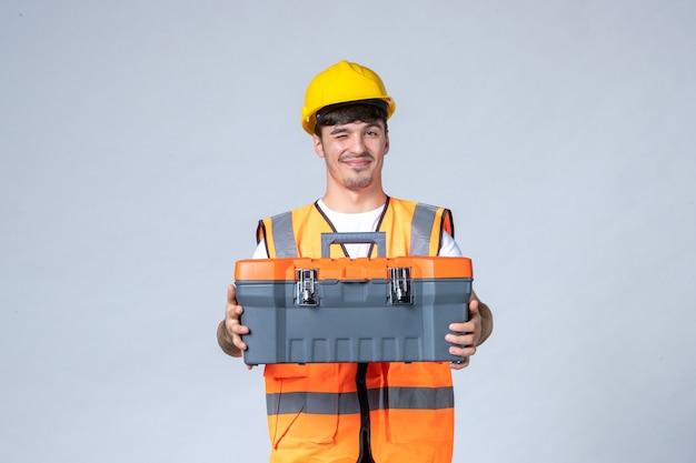 Vooraanzicht van mannelijke bouwer in uniforme en gele helm met gereedschapskoffer op witte muur