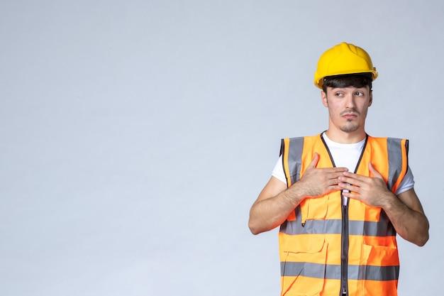 Vooraanzicht van mannelijke bouwer in uniforme en gele helm op witte muur