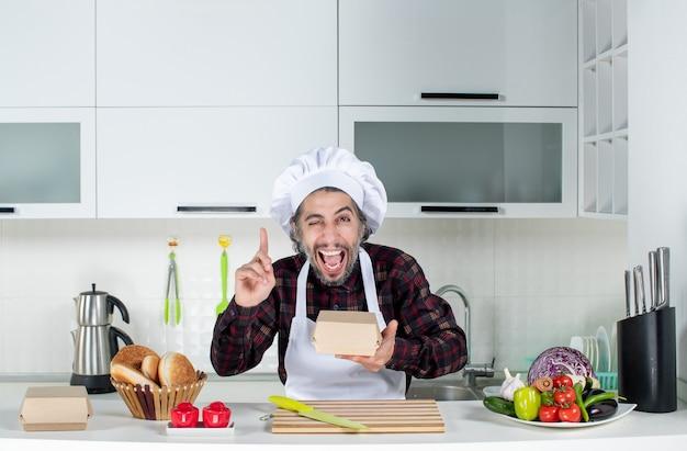 Vooraanzicht van mannelijke chef-kok die met de vinger omhoog wijst en een doos in de keuken vasthoudt