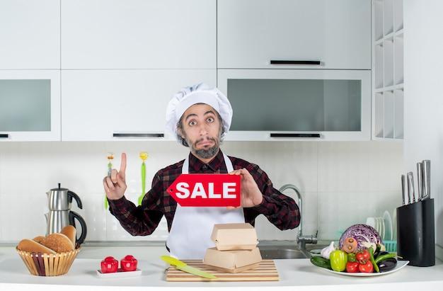 Vooraanzicht van mannelijke chef-kok die naar het plafond wijst en een verkoopbord in de keuken omhoog houdt