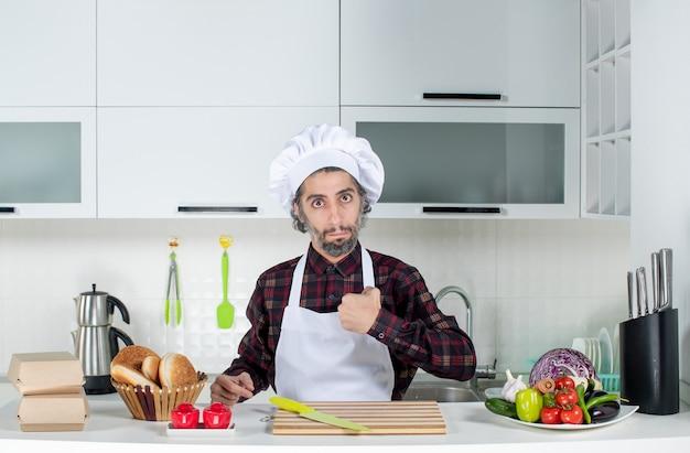 Vooraanzicht van mannelijke chef-kok die naar zichzelf wijst en achter de keukentafel in de keuken staat
