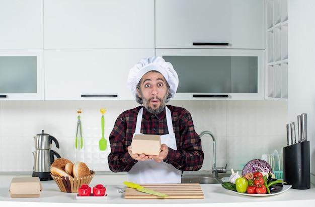 Vooraanzicht van mannelijke chef-kok in uniforme holdingsdoos in moderne keuken
