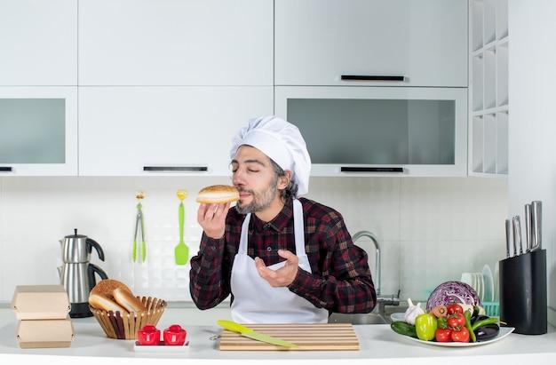 Vooraanzicht van mannelijke chef-kok met gesloten ogen die brood in de keuken ruikt