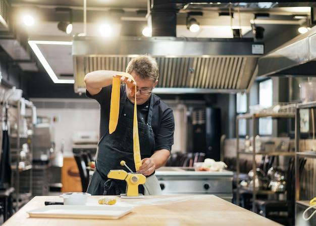 Vooraanzicht van mannelijke chef-kok rollende deegwaren