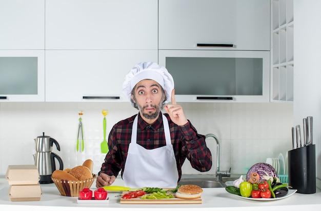 Vooraanzicht van mannelijke chef-kok verrassend met een idee in de keuken